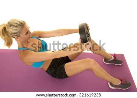 a woman doing a crunch with a weight. - stock photo