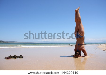 A woman doing a headstand on the beach
