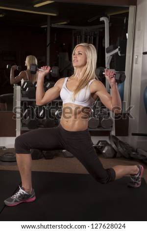 A woman doing a lunge and lifting weights with a smile on her face. - stock photo