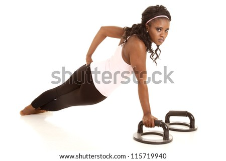 A woman doing a one arm push up with a serious expression on her face.
