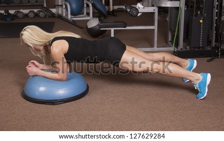 a woman doing a plank position in a gym. - stock photo