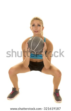 a woman doing a squat with a medicine ball.