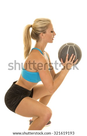 a woman doing a squat with a weighted ball.