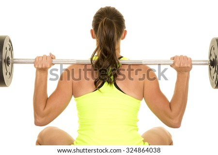 a woman doing a squat with a weighted bar across her back.