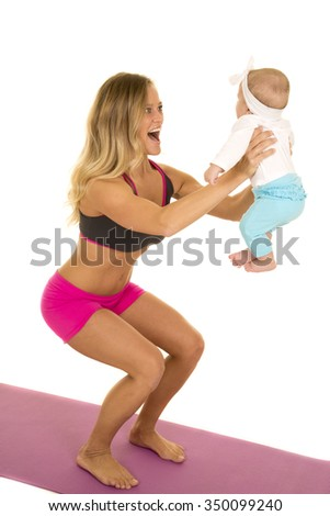 A woman doing a squat with her baby as her weight. - stock photo