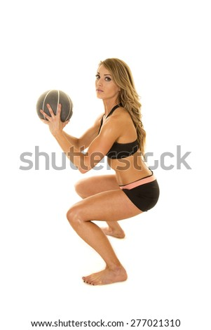 A woman doing a squat with her fitness ball in her hands. - stock photo
