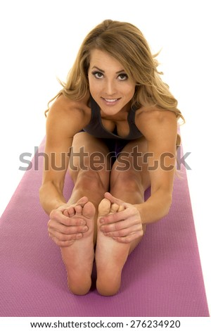 A woman doing a stretch, with a smile on her face.