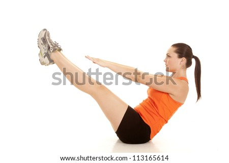 A woman doing a v up and exercising with a serious expression. - stock photo