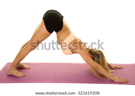 A woman doing a yoga stretch in her fitness clothing.