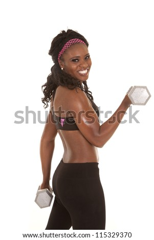 a woman doing an arm curl with a weight with a smile on her face. - stock photo