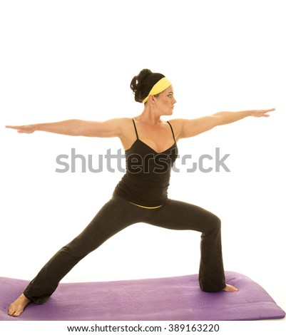 a woman doing her yoga stretch warrior to stretch out her body. - stock photo