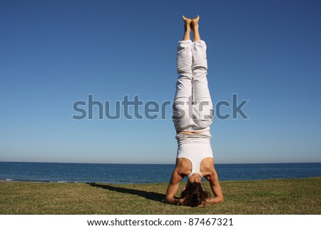 A woman doing yoga by the sea - stock photo