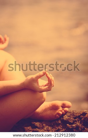 A woman doing yoga exercise and serenity at sunset - stock photo