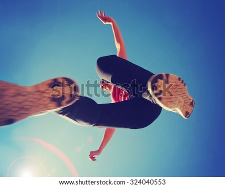 a woman dressed in active wear jumping directly over the camera with a wide angle lens during summer time with a lens flare in the corner - a unique perspective