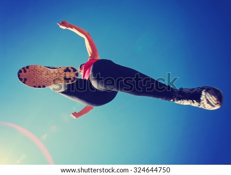 a woman dressed in active wear jumping directly over the camera with a wide angle lens during summer time with a lens flare in the corner - stock photo