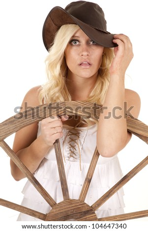 A woman dressed like a cowgirl is standing by a wagon wheel. - stock photo