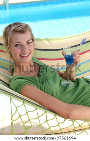 a woman drinking a cocktail near a swimming-pool - stock photo
