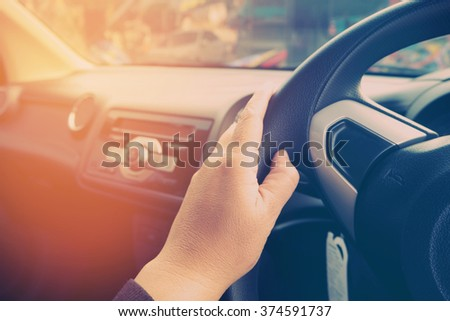 A woman driving a car with filtered image and vintage style.