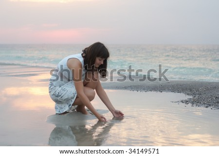 A woman early in the morning on the sea - stock photo