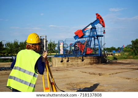 A woman engineer - land surveyor at work on an European oil well