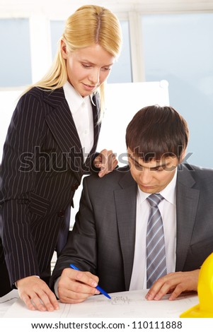 A woman engineer looking at plan with her colleague near by