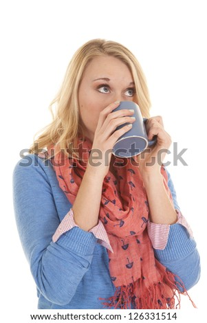 A woman enjoying a drink while she is wearing her scarf and sweater. - stock photo