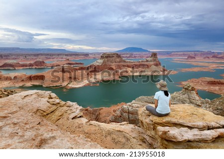 A woman enjoying the view from Alstrom Point, Lake Powell, Glen Canyon National Recreation Area. - stock photo