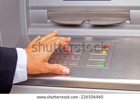 A woman enters her pin into the cash machine - stock photo