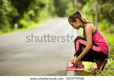 A woman fell Tie shoelaces While jogging - stock photo