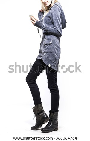 A woman(female, girl, model) wearing grey sweater(shirts, top, hood), black pants(jeans, denim, trousers), black boots(walker) hold smart phone(mobile) close up isolated white at the studio. - stock photo