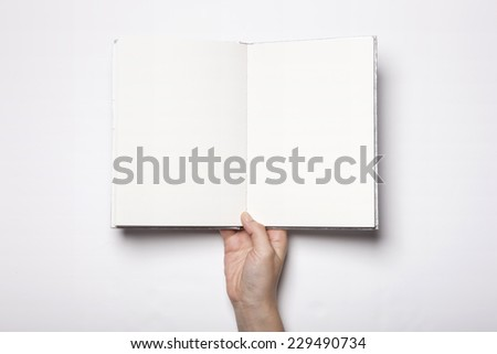 A woman(female) hand hold a empty(blank) book(note, diary) spread(unfold) isolated white, top view, studio. - stock photo