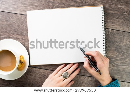 A woman(female) two hands hold a empty(blank) book(note, diary) spread(unfold) sketchbook top view. Designer draws sketches at the table coffee break. Inspiration. Beautiful silver jewelry.