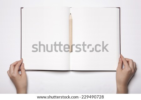 A woman(female) two hands hold a empty(blank) book(note, diary) spread(unfold) with wooden pencil isolated white, top view, studio. - stock photo