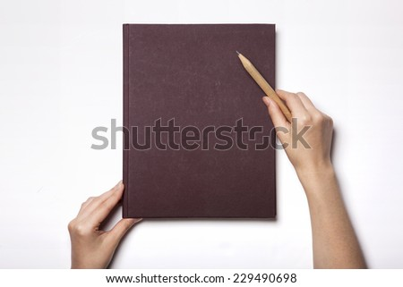 A woman(female) two hands hold a wine book(note, diary) cover with wooden pencil isolated white, top view, studio. - stock photo