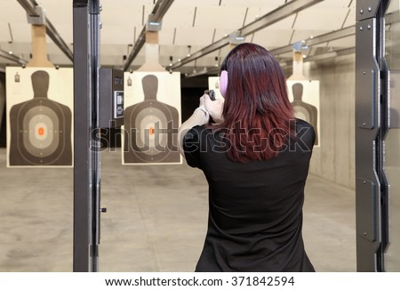 A woman firing a hand gun at an indoor gun range.
