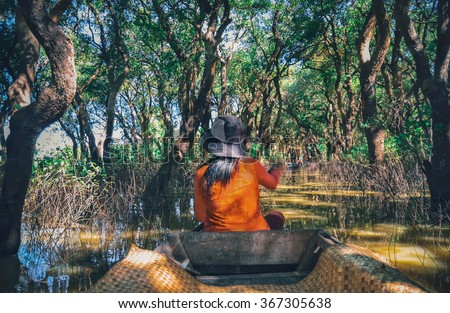 A woman floating on a boat in the village built on the Tonle Sap lake. People living on the water in the city of Siem Reap . Flooded trees in mangrove rain forest. Kampong Phluk village. Cambodia   - stock photo