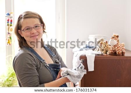 A woman folding baby clothes near a dresser. - stock photo