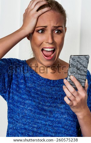 a woman gets bad news via sms and is shocked. - stock photo