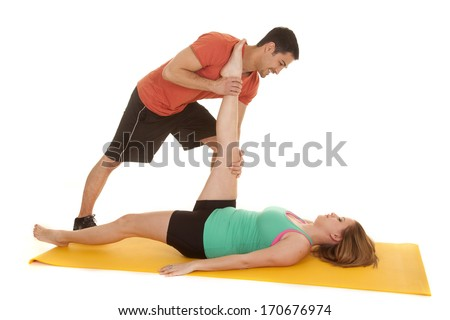 A woman getting her leg stretched by her man.