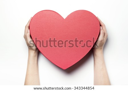 A woman(girl, female) hands hold a red heart(love) empty(vacant, hollow, blank) gift box(package, container) for christmas, birthday, holiday isolated white at the studio. - stock photo