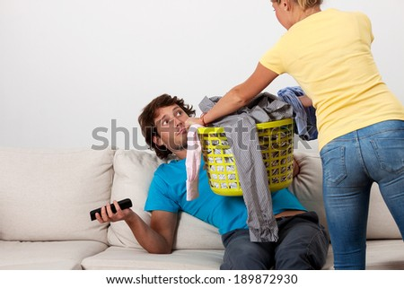 A woman giving her husband dirty clothes to do the laundry - stock photo
