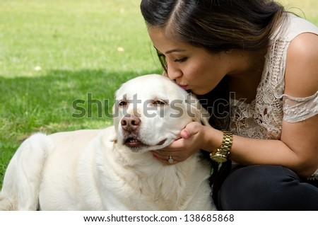 a woman giving her pet dog a kiss. - stock photo