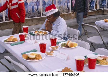 A woman giving thanks for her Christmas dinner, Los Angeles Mission, CA - stock photo