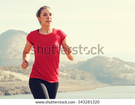 A woman going running next to some mountains