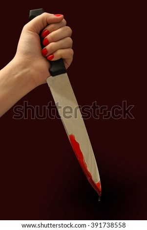 A woman grips a bloody knife in a killers pose.