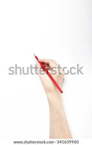 A woman hand hold a red pencil on the white desk(table, board) top view isolated white at the studio.