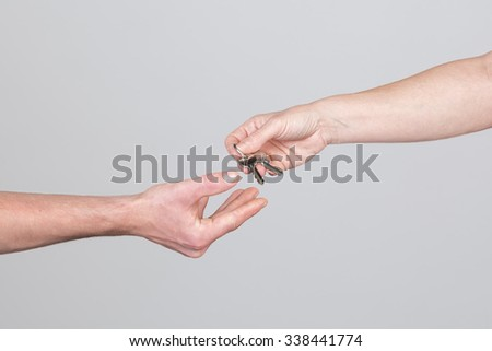 A woman hand is handing over a apartment key to a man, isolated on a grey background. - stock photo