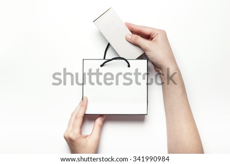 A woman hands hold a empty(blank, vacant, hollow) white paper bag and box for cosmetics, accessory, top view isolated white at the studio. - stock photo