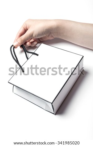 A woman hands hold a empty(blank, vacant, hollow) white small paper bag for cosmetics, accessory, top view isolated white at the studio. - stock photo