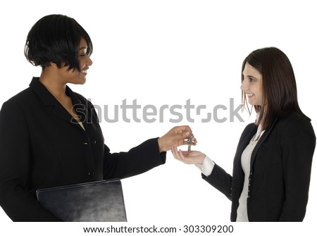 A woman hands over keys to another woman.